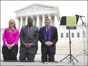 Rev. Rob Schenck, of Faith and Action, right, prays in front of the Supreme Court with Raymond Moore, and Patty Bills, both also of Faith and Action.