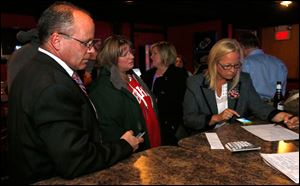 Bedford Schools superintendent Mark Kleinhans, Sandy Kraine, and board trustee Lisa McCaig tally school levy results at Sidelines in Lambertville, Mich.