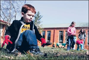 Ryan Brehmer, 3, helps weed a garden bed.