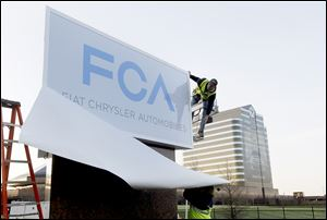 The Fiat Chrysler sign is unveiled at Chrysler World Headquarters in Auburn Hills, Mich.