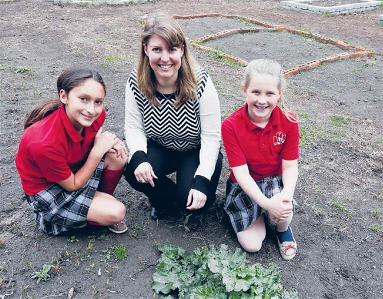 St-Pius-X-fifth-graders-Maria-Richard-left-and-Lauren-Hitts-with-teacher-Jen-Ohms