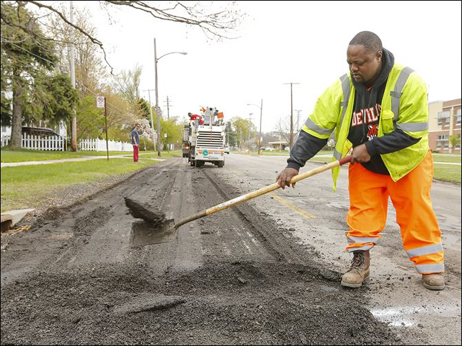 08n5potholes Senior utility worker Shawn Jordan helps remove asphalt as crews work on Detroit Avenue. City crews are fixing as many roads as possible this week.