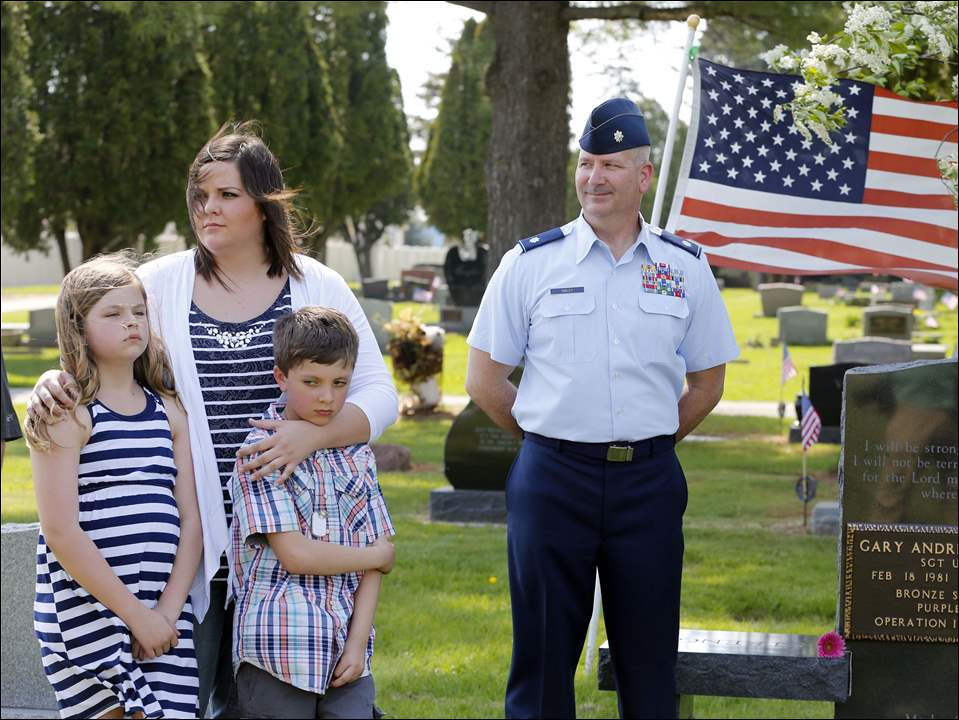 Left to right  Marlee Eckert, 10, Tiffany Eckert, Myles Eckert, 9, and Lt. Col. Frank Dailey during a ceremony for Sgt. Andy Eckert.