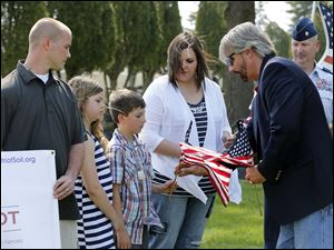 Kentuckyana Jones, from A&E television, presents American flags to Marlee Eckert, 10, Myles Eckert, 9, and Tiffany Eckert, as Sgt. Jeremy Langham, left,  and Lt. Col. Frank Dailey, right, look on.