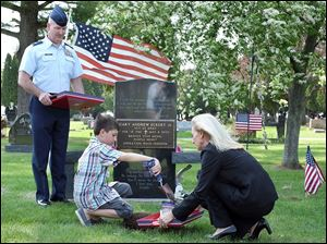 Myles Eckert, 9, shovels dirt from the grave of his father, Sgt. Andy Eckert, into a vessel held by Mary Robinson of the Patriot Soil Project as Lt. Col. Frank Dailey looks on at Whitehouse Cemetery.  Sergeant Eckert died while serving in Iraq nine years ago on Thursday.