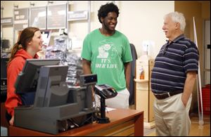 Dick Larabee, 79, talks with Ron Freeman, a junior at Bowling Green State University, at the campus bookstore. Mr. Larabee, who lives in Waterville, will receive a bachelor's degree in liberal studies during spring commencement ceremonies.