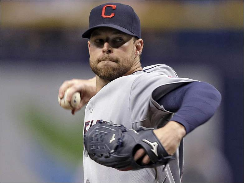 Cleveland Indians starting pitcher Corey Kluber goes into his windup against Tampa Bay Rays' James Loney.
