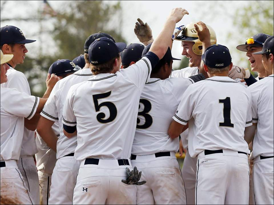 St. John's Jesuit first baseman Pete Burkett (21) celebrates hitting a home run against  St. Francis with teammates during the fourth inning.