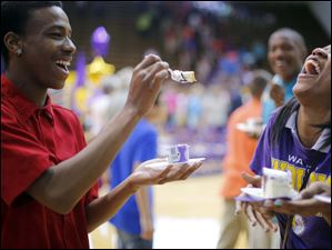 Daveon Lofton, left, has a laugh with fellow sophomore Dajanay Wells as he offers to feed her cake.