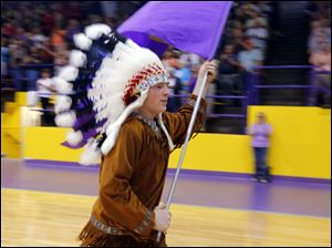 Waite Indian mascot Jason Kendall, a junior at the school, races through the Grant Murray Field House carrying the school's flag.