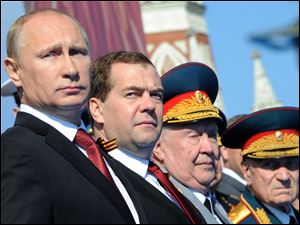 Russian President Vladimir Putin, left, and Prime Minister Dmitry Medvedev attend a Victory Day parade, which commemorates the 1945 defeat of Nazi Germany, at Red Square in Moscow, Russia, today.