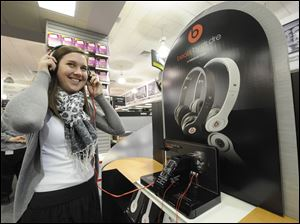 A customer tests out the sounds of Beats by Dr. Dre headphones at a Staples store in New York City