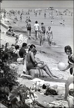 Swimmers and sunbathers enjoy the East Harbor beach four months before a storm destroyed it in 1972.