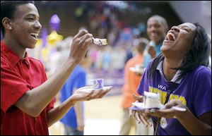 Daveon Lofton, left,  laughs with fellow Waite sophomore Dajanay Wells as he offers to feed her cake after the ceremony. Another event is set for today.