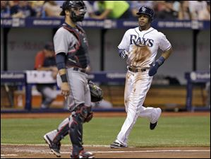 Tampa Bay Rays' Desmond Jennings, right, scores in front of Cleveland Indians catcher Yan Gomes on an RBI-single by teammate David DeJesus.