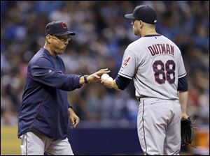 Indians manager Terry Francona, left, takes the ball from relief pitcher Josh Outman.
