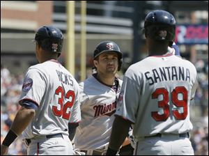 Minnesota Twins' Brian Dozier, center, is greeted by teammates Aaron Hicks (32) and Danny Santana (39) after they scored on Dozier's three-run home run.