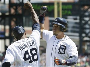 Detroit Tigers' Miguel Cabrera is congratulated by teammate Torii Hunter after they scored on Cabrera's 3-run home run.
