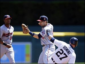 Brian Dozier bobbles the throw from catcher Kurt Suzuki and allows Detroit Tigers' Andrew Romine to reach second.