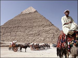An Egyptian camel rider waits for customers at the historical site of the Giza pyramids, in front of the Khafre pyramid, near Cairo.