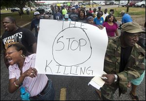 K.K. Davis, left, and Tommy Jones of Hearne carry a sign with other protesters outside the Hearne, Texas police department.