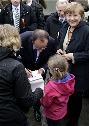 German Chancellor Angela Merkel, right, smiles as President of France Francois Hollande, center, gives an autograph to 6 years old tourist Hanna during a visit today in northern Germany.