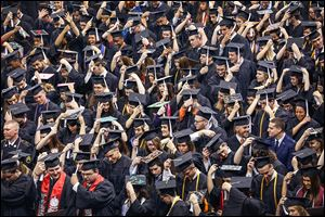 Graduates move their tassels to the left side of their caps at the 279th commencement at Bowling Green State University in Bowling Green. A total of 2,260 degrees were awarded to the class of 2014.
