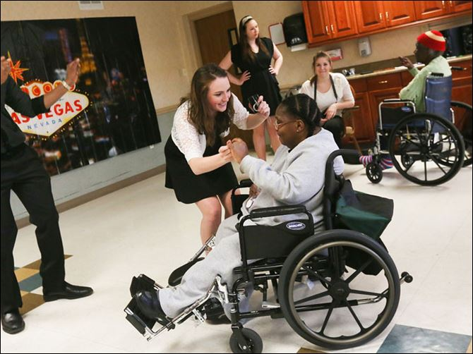 Adopt-A-Grandparent Nonso Agubosim, left, watches Ashley Wolfenbarger, center, dance with Stacye Griffin at The Laurels during a prom sponsored by the organizaton Adopt-A-Grandparent.