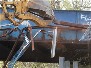 Work begins with the destruction of the pedestrian walkway, which was on the northwest side of the bridge.