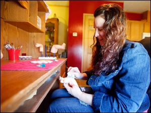 Jennifer Neal works to make a baby doll at her desk in her home business called Reborn Nursery in Elmore.