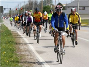 Oregon resident John Gray leads a pack of cyclists making their way down Fort Meigs Road.