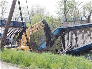 The excavator cuts through the far wall, disconnecting the two halves of the bridge.