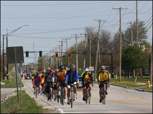 Cyclists make their way down Fort Meigs Road.