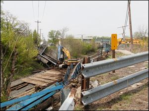 Timbers on the rails give the large excavator a place to work and protects the rails from the falling debris.