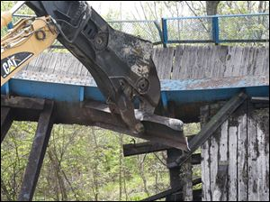 The excavator twists a steel beam to detach it from the bridge.