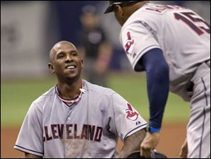 Indians first base coach Sandy Alomar Jr. picks up the helmet of Nyjer Morgan, left, after a close play that was ruled safe on a reversal.