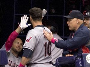 Cleveland Indians' David Murphy, left, and bench coach Brad Mills, right, greet Yan Gomes in the dugout after his solo home run.