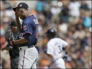 Twins starting pitcher Samuel Deduno reacts after giving up a solo home run to Detroit Tigers' Ian Kinsler, background,