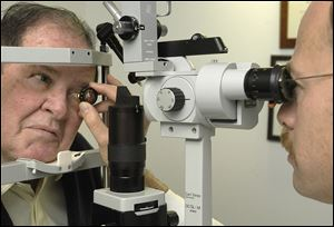 Dr. Ira Orgel examines the eyes of  John Taft for macular degeneration treatment.