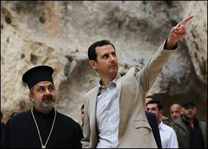 Syrian President Bashar Assad, right, visits the Ch