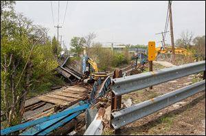 The Curtis Street bridge, built in 1899,  is pulled down. Longtime residents say the bridge was a prominent part of their childhood.