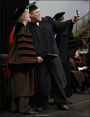 BGSU president Mary Ellen Mazey poses with graduate Dylan Burley as he takes a selfie.