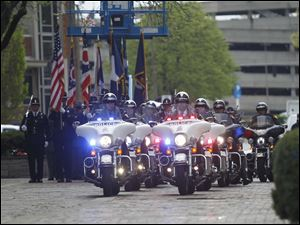 A line of police motorcycles rides at the start of the annual memorial service.