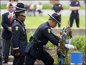 Members of the Toledo Police Department, including Chief William Moton, left, present the wreath.