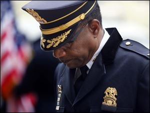 Chief of Police William Moton bows his head.