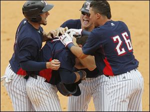 Brandon Douglas, second from left, is congratulated by Ben Guez, left, Casey Crosby, and Hernan Perez after he singled to center to plate the winning run for the Hens