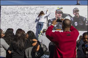 Fans crowd the scene of a memorial rally and car cruise in Valencia, Calif., to remember actor Paul Walker and his friend Roger Rodas, who died in a fiery car crash in this 2013 file photo.