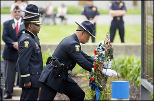 Toledo police Chief William Moton, left, and Officer Thomas Killen present the wreath during a ceremony Monday to honor officers killed in the line of duty. The law enforcement family who gathered in Toledo did so to keep a promise they had made to never forget.