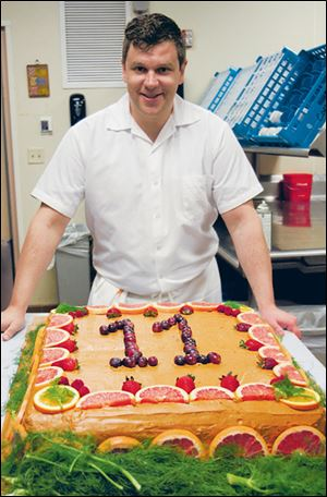 Chef Sam with Louie the elephant's birthday cake of polenta and peanut butter icing and decorated with fruit.