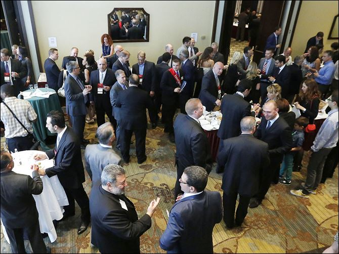 0001040100000000000  Italian and American businessmen mingle at Italian Business Forum in Toledo on Monday night.